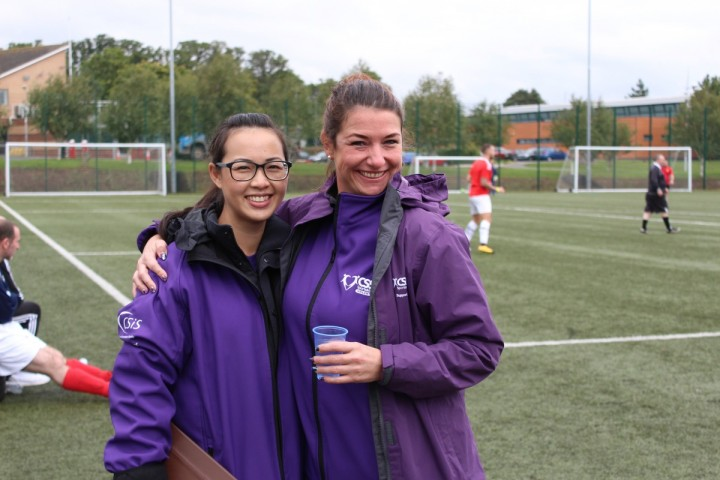Two women wearing purple CSSC volunteer coats and jackets smile for the camera at the side of a football pitch