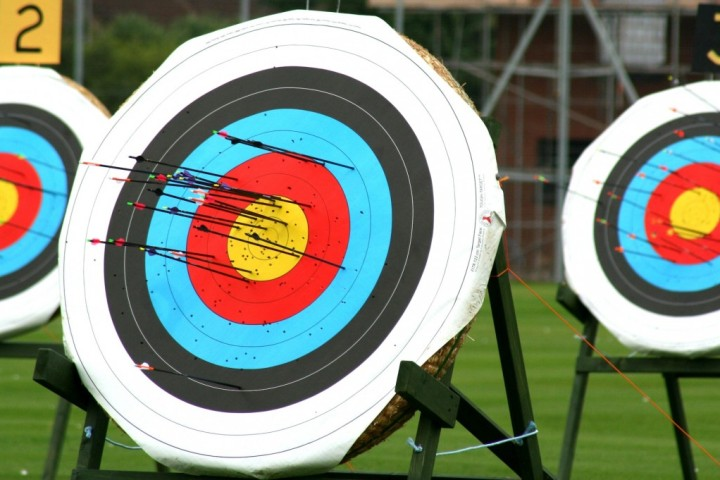 Three archery boards with colourful targets and many arrows embedded