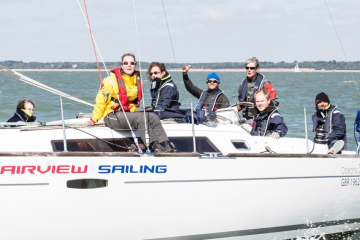 A group of people smile for the camera on a sailboat emblazoned 'Fairview sailing'