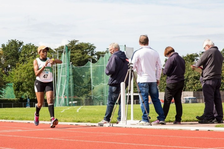 A runner checks their time whilst running on an outside athletics track
