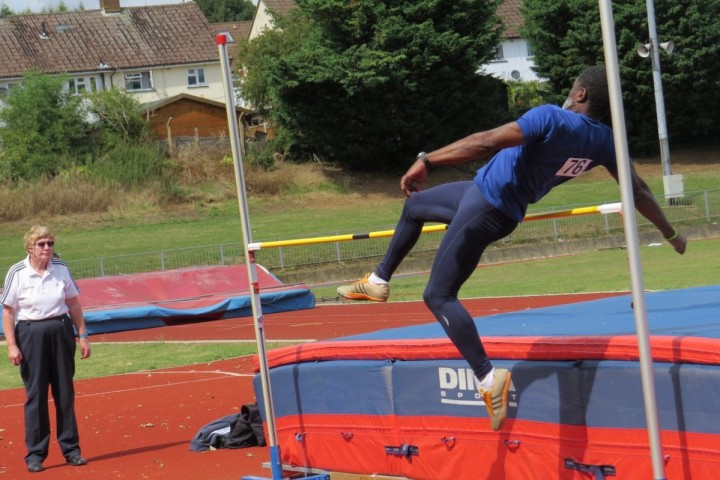 A man is mid-highjump, just about the clear the bar