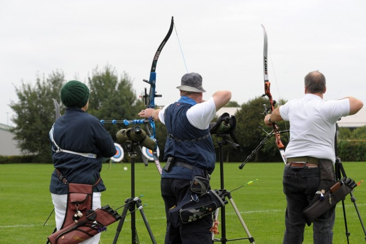 A view from the back of two people holding their bows taut, about to shoot an arrow