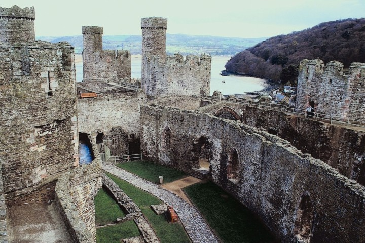 A view of the courtyard and castle wall ruins, the sea can be seen behind the castle with a hill on the right
