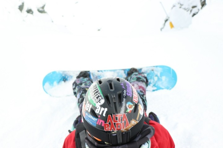 Snowboarder sitting down on a slope.