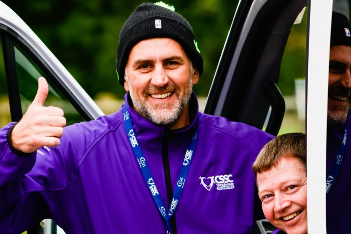 A man wearing a purple CSSC branded volunteer hoody and CSSC lanyard smiles and signals a thumbs up to the camera