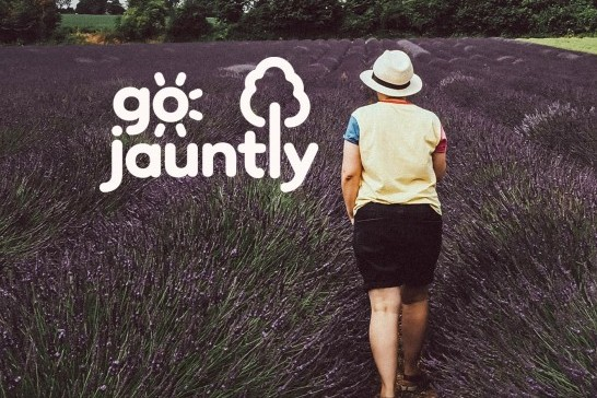 A person is walking through a field into the background. The Go Jauntly logo is overlayed, the 'o' in 'go' is a sun and the 'l' in 'jauntly' is a tree