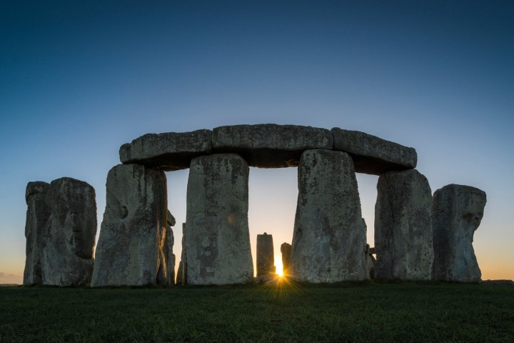 The setting sun can be seen between the silhouetted stones of stonehenge