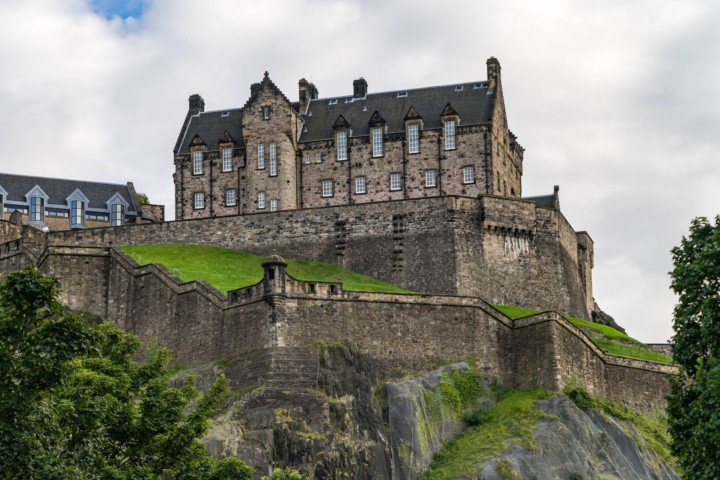 Edinburgh Castle is perched on top of a hill, with an outer wall running along the hillside, all covered in a light layer of snow
