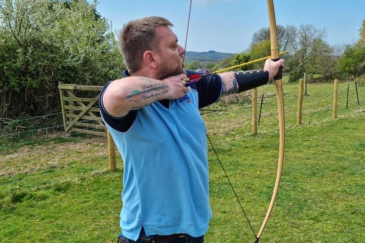 Matt holding his archery bow